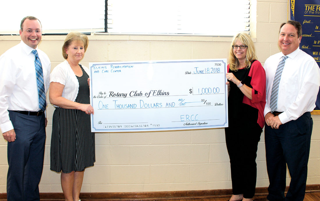 The Inter-Mountain photo by Brooke Binns On behalf of Elkins Rehabilitation and Care Center, Betsy Jones, chief financial officer, second from left, and Tara Shaver, administrator, present the Rotary Club of Elkins with a $1,000 donation for the club's amphitheater project in the Elkins Town Square. Also pictured are Hoy Ferguson, past Rotary president, left, and Carl Nichols, Rotary president.